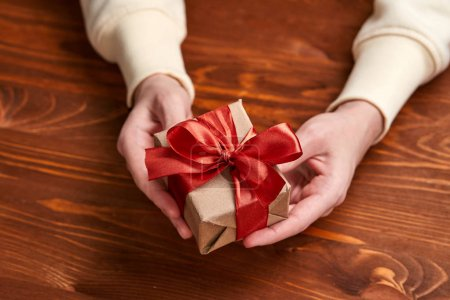 Photo for Hands holding craft gift box, close-up - Royalty Free Image