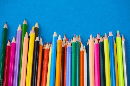 Foto de Surtido de lápices de colores sobre fondo azul, primer plano - Imagen libre de derechos