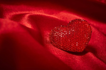beautiful red decorative heart for Valentines day on beautiful red silk fabric, close-up