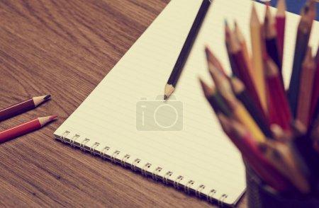 Photo pour Bloc-notes et crayons sur table en bois, vue rapprochée - image libre de droit