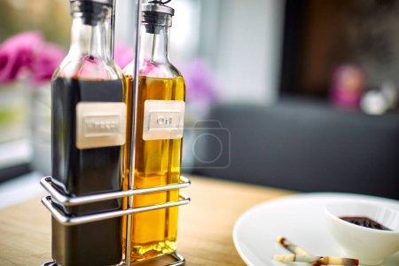 Photo pour Huile d'olive et vinaigre balsamique sur table en bois au café - image libre de droit