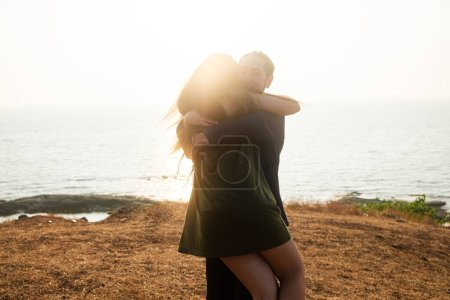Photo for Backlit Portrait of a young romantic couple swirls in a hug against the backdrop of the sea. Anjuna Hills, Goa, India - Royalty Free Image