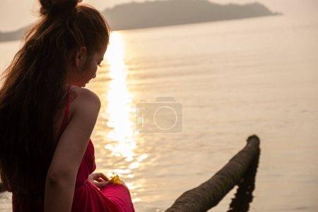 Photo pour Femme assise sur un palmier, admirant le coucher du soleil sur Chapora, GOA, Inde - image libre de droit