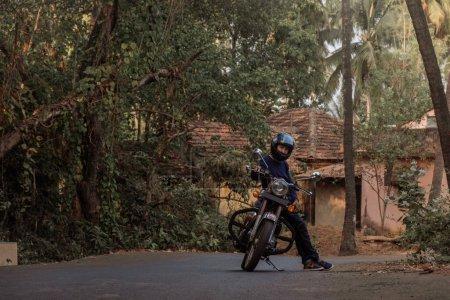 Photo pour Un homme à moto Sur la route dans le village de GOA - image libre de droit