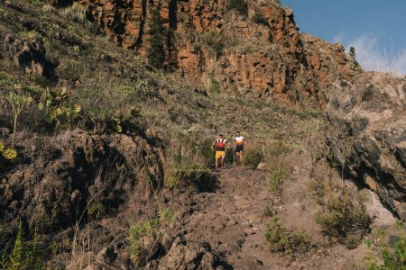 Photo pour Groupe de jeunes adultes s'entraînant et courant ensemble à travers des sentiers sur la colline à l'extérieur dans la nature. Adaptez le sentier des jeunes à un sentier de montagne. - image libre de droit