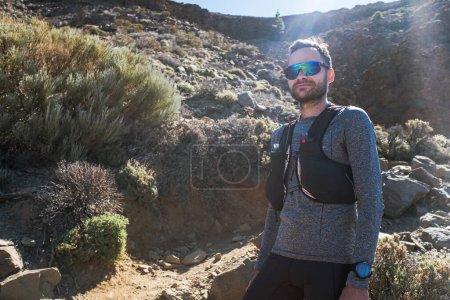 Foto de Retrato de un hombre caucásico joven y saludable en el equipo de pie al aire libre y sonriendo. Joven corredor de confianza en la carretera del campo. - Imagen libre de derechos