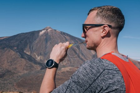 Photo for Portrait of young man drinking sports nutrition energy gel while sitting and resting after trail running on mountain peak - Royalty Free Image