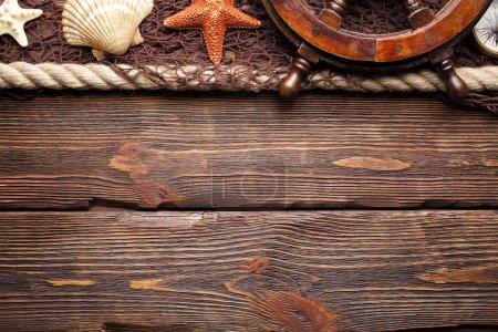 Marine background - fishing net, ship's steering wheel, hawser ans seashells on wooden board