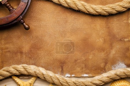 Ship's steering wheel, hawser and seashell on paper and sand background
