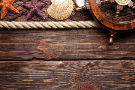 Marine background - fishing net, ship's steering wheel, hawser ans seashells on wooden board