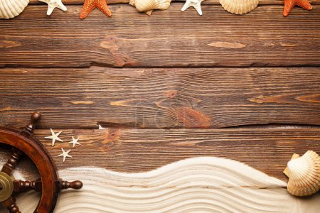 Ship's steering wheel, beach sand and shells on wooden wall background