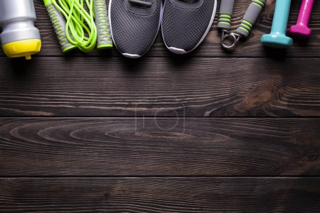 Photo for Fitness equipment - water, jumping rope, sneakers and dumbbell on wooden board - Royalty Free Image