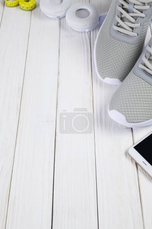 Photo for Smartphone, earphones, sport shoes, and measuring tape on wooden board - Royalty Free Image