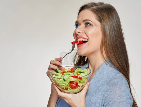 Photo for Casual dressed smiling woman holding glass bowl and eating salad - Royalty Free Image