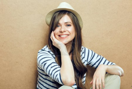 Photo for Portrait of young smiling woman wearing hat and striped shirt looking at camera and sitting near beige wall - Royalty Free Image