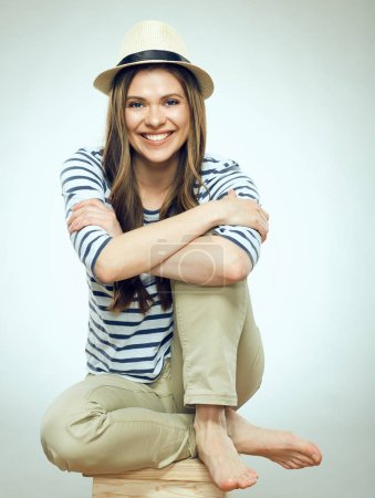 portrait of smiling woman wearing hat sitting on wooden bench