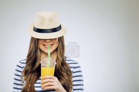 funny portrait of smiling woman with hat on eyes drinking orange juice
