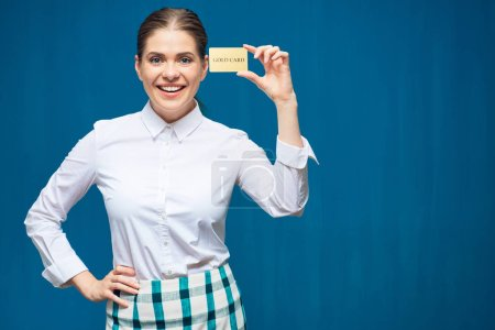 Smiling woman holding credit card on  Blue background