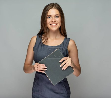 Smiling teacher with book in hands standing against gray wall