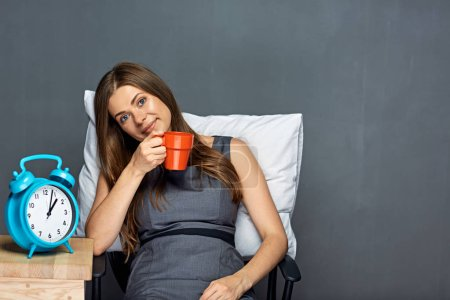 Businesswoman sitting in office chair with pillow and coffee cup,  Working break concept