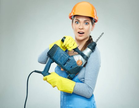 surprised woman builder in safety helmet and overall holding drill tool, hard work concept