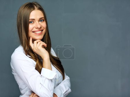 Young woman wearing white shirt posing against grey wall background