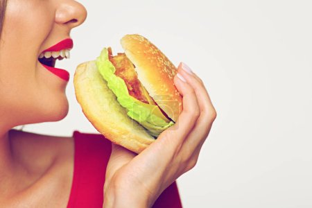 woman with opened mouth biting burger isolated on white background, close-up