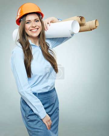 Young business woman engineer, architect holding rolled up technical drawings. Isolated studio portrait.