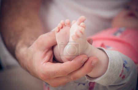 newborn baby feet in male hands