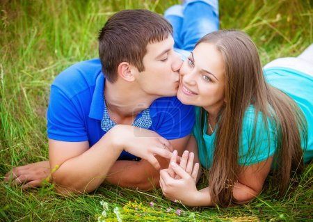 Romantic couple having fun and kissing relaxing in field