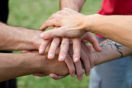 Photo for Cropped image of team of sportsmen putting hands together at lawn - Royalty Free Image