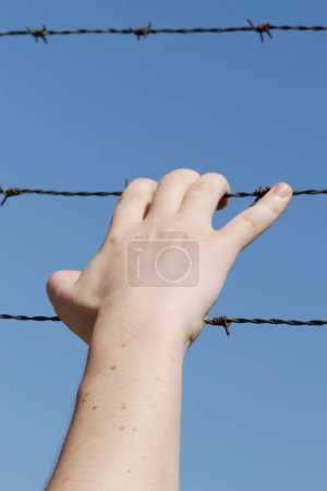 Hand of teenager on barbed wire against blue sky