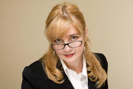 Photo for Portrait of blonde businesswoman wearing eyeglasses smiling posing on beige studio background - Royalty Free Image