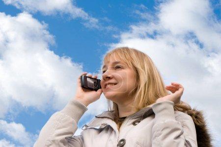 Photo pour Vue de fond de femme dans la veste d'hiver parlant par téléphone devant le ciel - image libre de droit