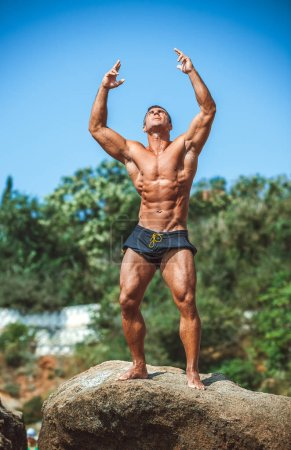 Photo for Handsome male athlete posing on rocks - Royalty Free Image