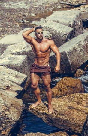 Photo pour Bel athlète masculin posant sur des rochers - image libre de droit
