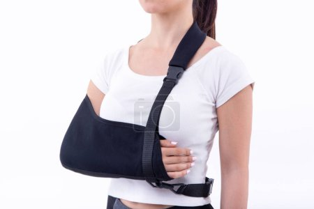 Photo pour Femme avec main cassée portant une attelle de bras sur fond blanc - image libre de droit