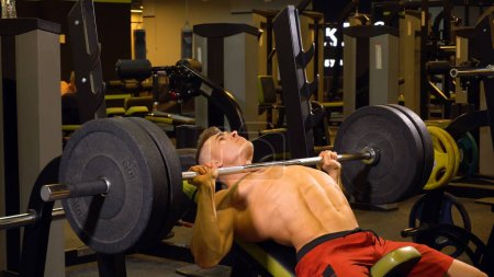 Photo for Strong man doing exercises in gym with barbell - Royalty Free Image