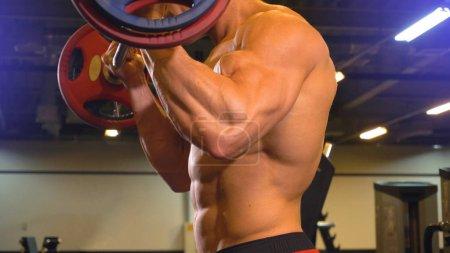 Photo pour Corps de l'athlète homme faisant biceps exercice avec haltère dans la salle de gym sans t-shirt - image libre de droit