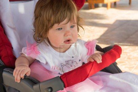 Photo pour Petite fille à la recherche de suite avec excité d'expression du visage tout en étant assis dans la poussette sur resort journée ensoleillée - image libre de droit