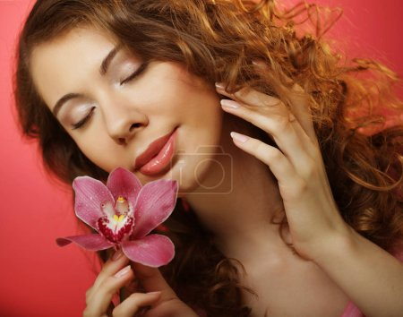 Photo for Beautiful happy curly woman with orchid flower over pink background - Royalty Free Image