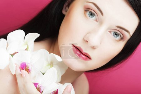 Photo for Beautiful healthy woman with orchid flower. Over pink background. - Royalty Free Image