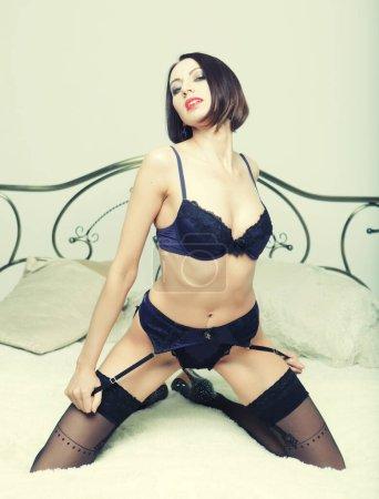 Photo for Striptease dancer on bed. Studio shot. - Royalty Free Image