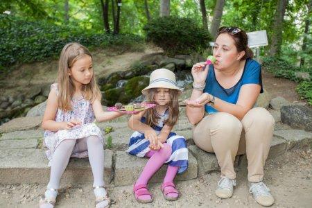 Photo pour Mère et deux petites filles au pique-nique dans le parc, jouant dans la nature . - image libre de droit
