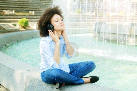 Portrait de belle mixte Jeune femme écoutant de la musique avec casque sans fil en plein air