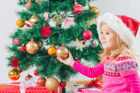 Photo for Happy Christmas child with gift box and new year tree at home. - Royalty Free Image