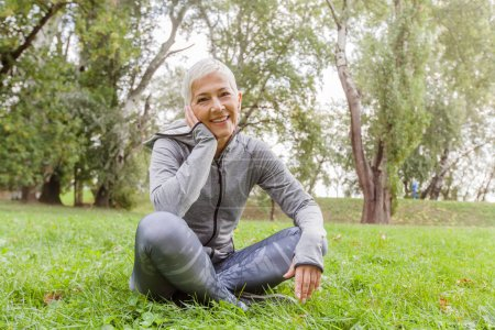 Photo for Portrait Of Happy Senior Woman Relaxing In Nature, Old Woman Sitting On Green Grass At The Park. - Royalty Free Image
