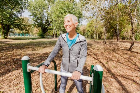 Elderly Woman In Sports Clothes Exercising At Outdoor Fitness Park, Healthy Lifestyle Mature People.