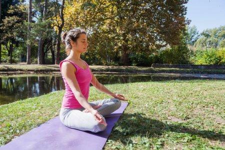 Photo pour Femme Méditant Et Pratiquant Le Yoga Au Parc Sur La Belle Journée Ensoleillée D'automne - image libre de droit