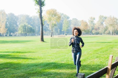 Photo for Healthy activity in park,Fitness African woman jogging at green fields in nature - Royalty Free Image